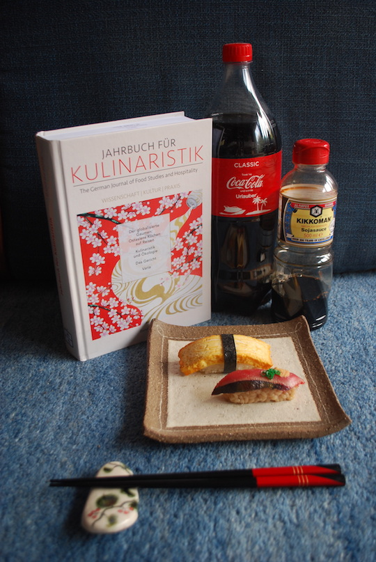 Jahrbuch für Kulinaristik, Cola-Flasche, Flasche Soja-Sauce, Tablett mit zwei Sushi, Stäbchen auf Ablage