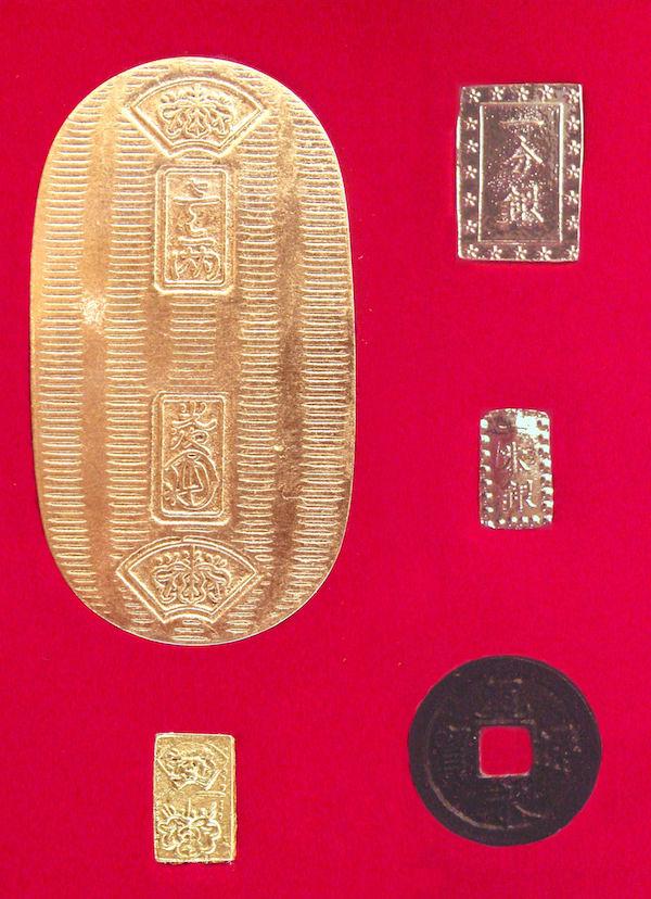 Münzen der Edo-Zeit von ungefähr 1714: zwei goldene (einmal oval, groß; einmal klein und rechteckig), zwei rechteckige silberne von unterschiedlicher Größe und eine runde Kupfermünze mit einem rechteckigen Loch in der Mitte.