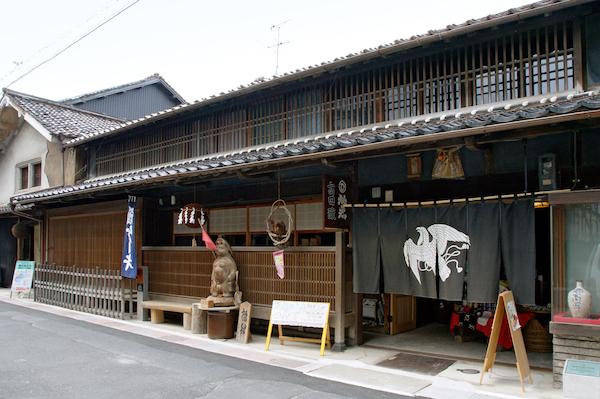 Front eines traditionellen Holzhauses mit einem breiten Vorhang (noren) vor dem Eingang. Motiv des Wappens auf dem Vorhang: ein fliegender Vogel.
