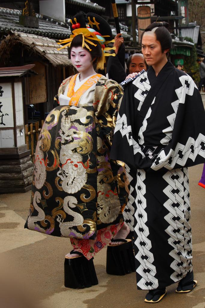 Straße vor den Kulissen des Themenparks Edo Wonderland mit einer Schauspielerin, die eine hochrangige Kurtisane darstellt, rechts neben ihr: ihr Begleiter