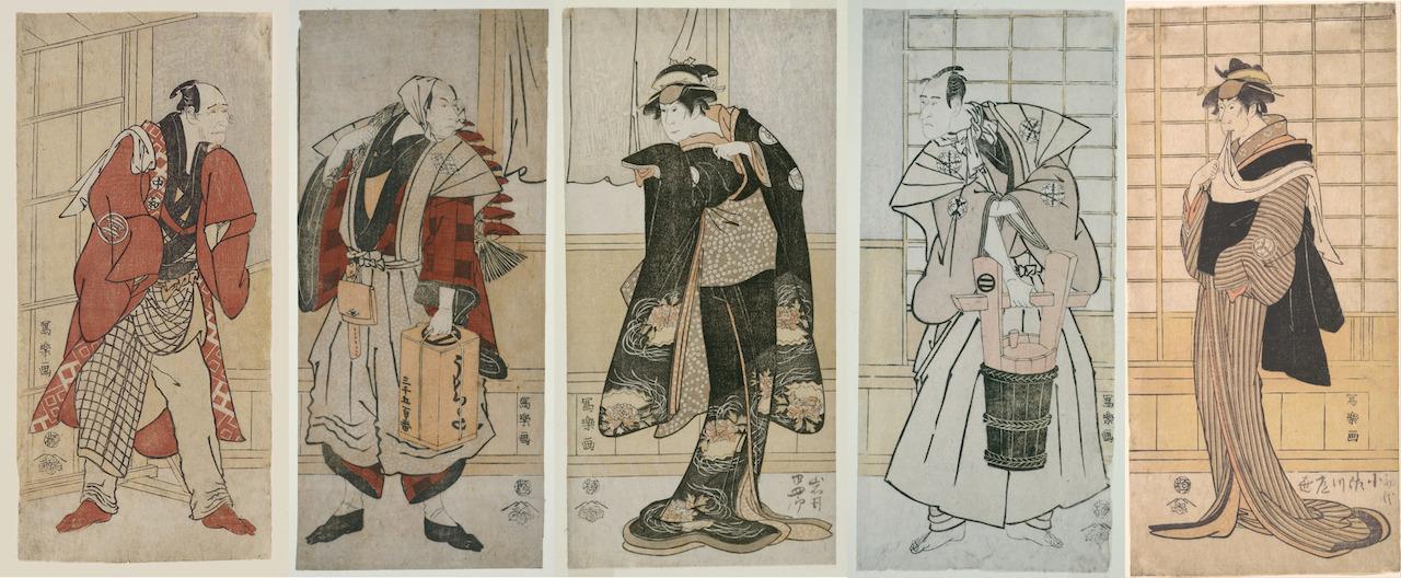 5 männliche Kabuki-Darsteller in verschiedenen Rollen, drei davon sehr stark und männlich, zwei von schmaler Gestalt, in Damen-Kimonos gekleidet und mit Haarspangen in den Haaren.