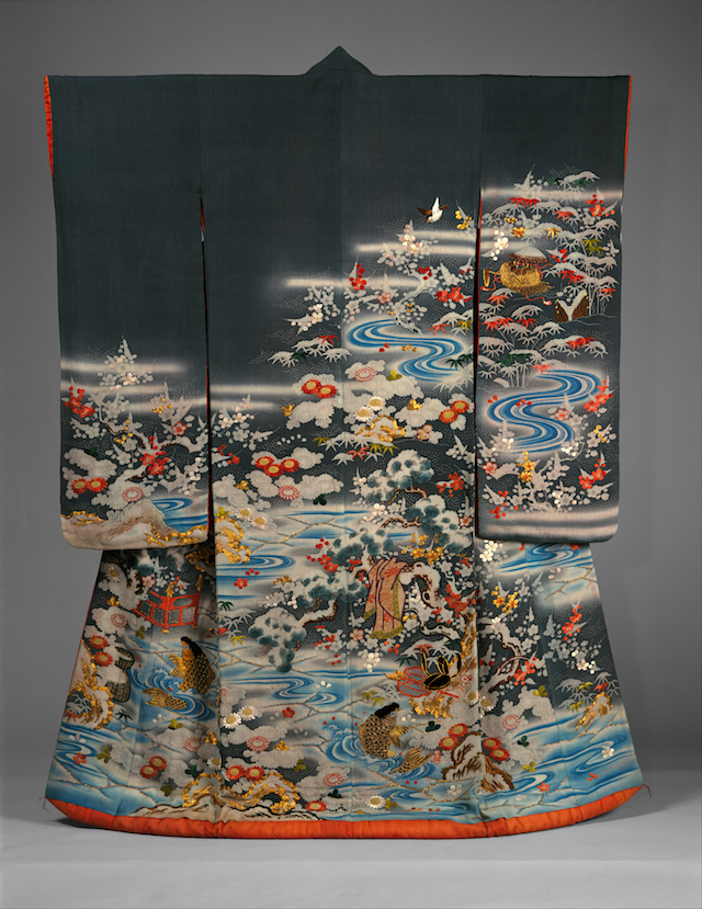 Furisode, d.h. Kimono mit sehr langen Ärmeln, in Dunkelblau. in den unteren zwei Dritteln mit einer üppigen Flusslandschaft, mit Kiefern und Blüten reich bestickt. Es dominieren die Farben Gold, Hellblau, Rot und Weiß.