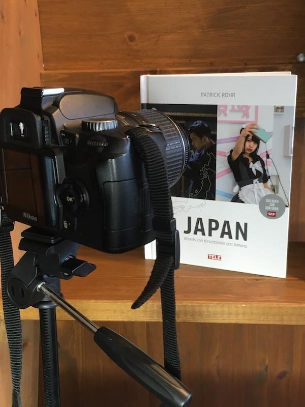 """Nikon-Kamera auf Stativ ist auf das Buch """"Japan - Abseits von Kirschblüten und Kimono"""" von Patrick Rohr gerichtet"""
