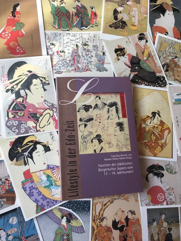 """In der Mitte des Bildes liegt das Buch """"Lifestyle in der Edo-Zeit"""", außenherum etwa 20 Postkarten mit Reproduktionen von Holzblockdrucken mit Kurtisanen und Schauspielern"""