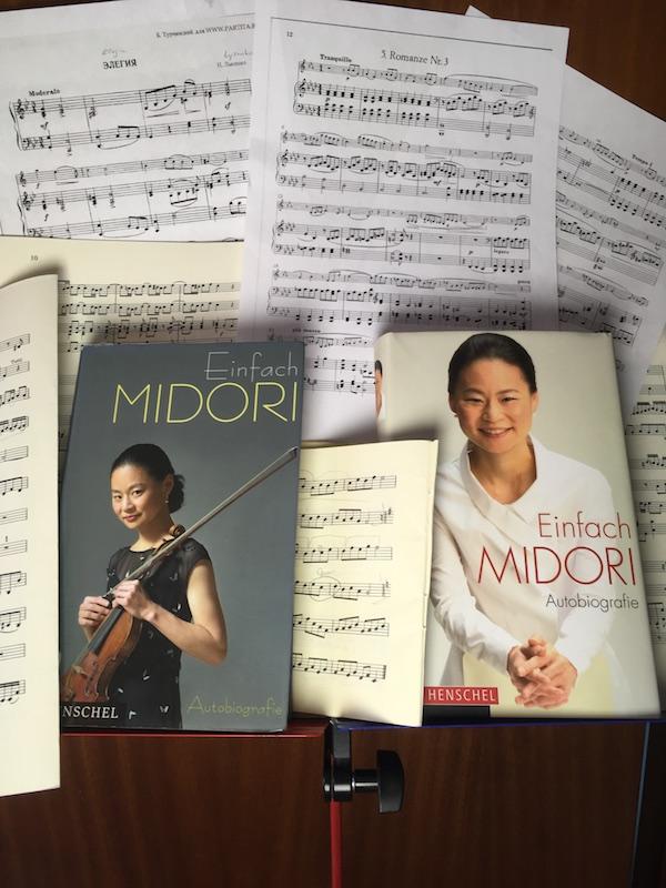 Auf einem Notenständer liegen die 1. und die 2. Ausgabe der Autobiografie von Midori, dazwischen und außen herum viele Notenblätter