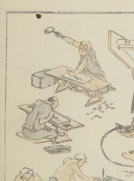 Ausschnitt aus einer Doppelseite der Hokusai Manga: zwei Schnitzer, die vor ihren niedrigen Arbeitstischchen sitzen und Vertiefungen aus den Holzblöcken herausarbeiten.