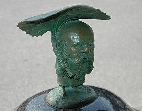 Koroppukuru: Kleine Figur eines alten Mannes mit übergroßem Kopf und längerem Bart, der in der rechten Hand wie einen Regenschirm ein originalgroßes Blatt der asiatischen Pestwurz trägt.