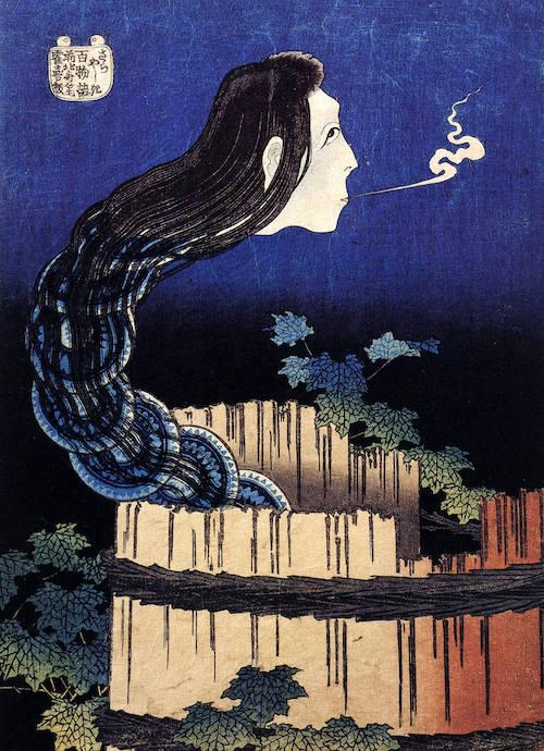 Ein Kopf mit langen, schwarzen Haaren steigt aus einem Brunnen hervor, unter den Haaren ist eine Reihe von Tellern zu sehen.