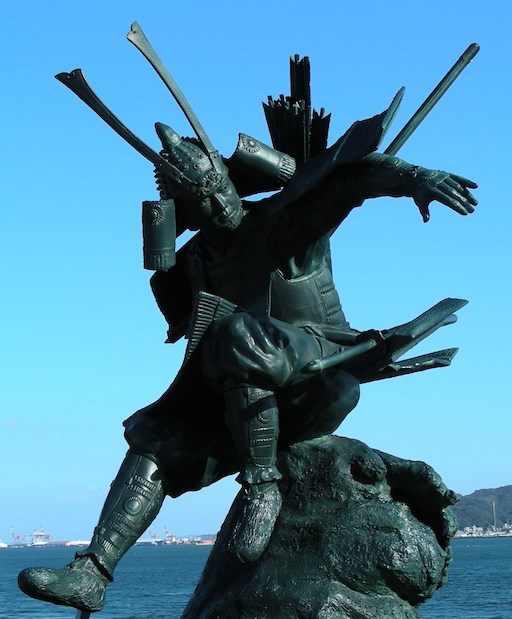 Eine Statue von Minamoto von Yoshitsune: Der Krieger Minamoto von Yoshitsune im eleganten Sprung von einem Fels.