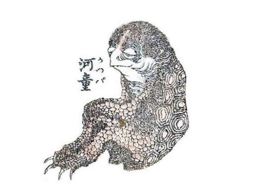 Ausschnitt aus einer Seite von den Hokusai Manga: ein Kappa, ein Flusskobold mit menschenähnlichen und reptilienhaften Zügen. Er sitzt wie eine Menschengestalt am Boden und stützt seine Arme auf die Knie.