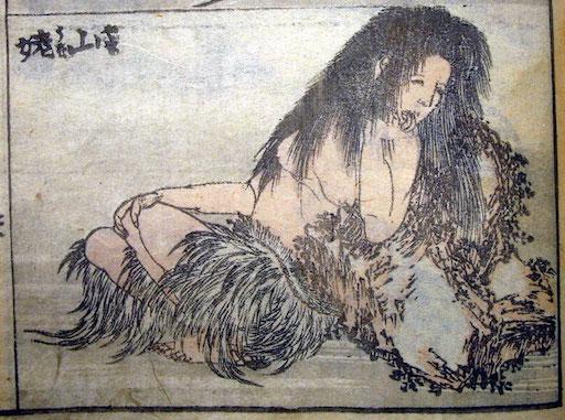 Ausschnitt aus einer Seite aus den Hokusai Manga: Die Berghexe Yamauba mit langen, schwarzen Haaren und nacktem Oberkörper sitzt an einen Felsen gelehnt.