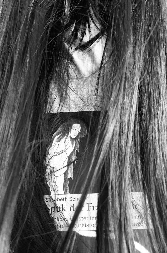 Buch vor weißem Gewandt, fast von langen schwarzen Haaren verdeckt