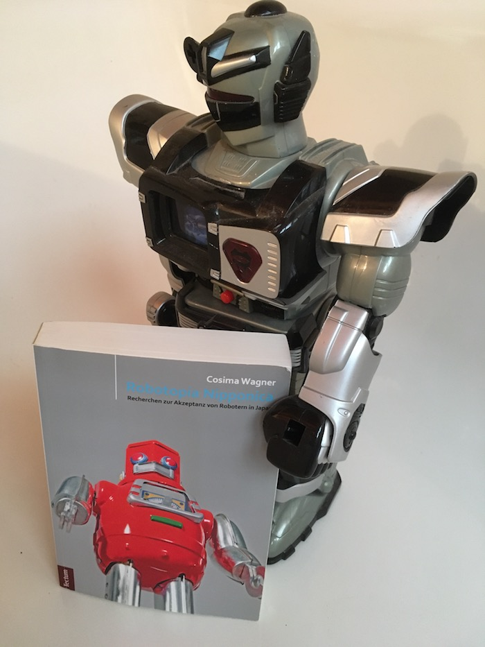 Spielzeug-Roboter der das Buch von Cosima Wagner im Arm hält