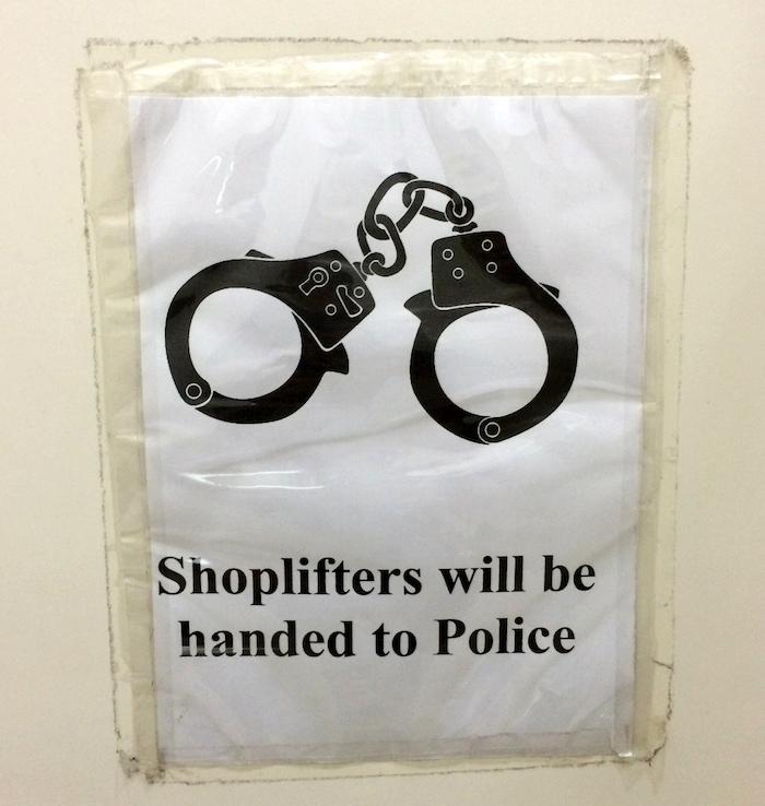 """In Plastik eingeschweißtes Papier, mit Klebestreifen an die Wand geheftet. Abgebildet sind Handschellen, darunter die Aufschrift: """"Shoplifters will be handed to Police""""."""